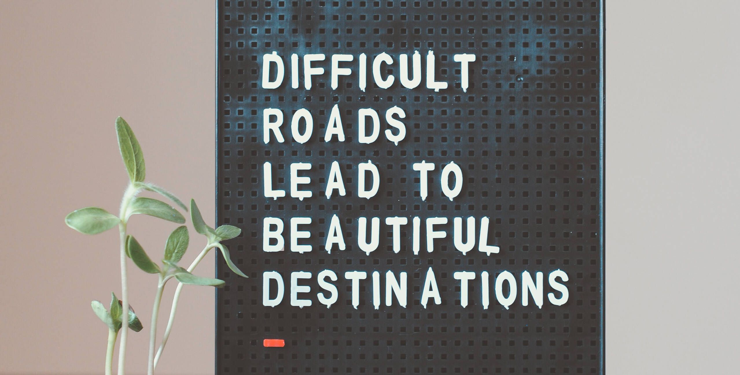 """Clipboard with """"Difficult roads lead to beautiful destinations"""" text"""